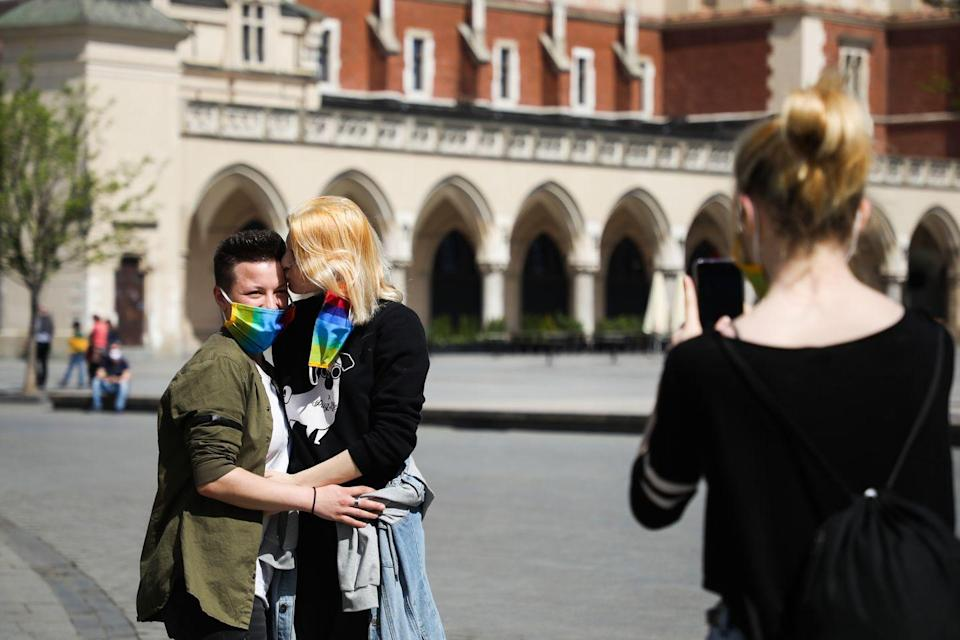 <p>Coupling and adhering to the new reality while taking a picture in Krakow, Poland. </p>