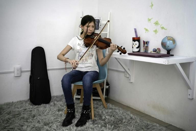 Paola, one of thousands of Mexican children who have lost a parent to Covid-19, plays the violin at her home in the eastern state of Veracruz