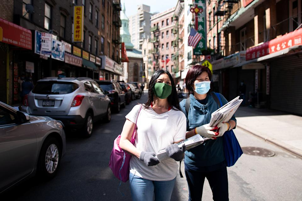 Shirley Ng (l) , a volunteer with the Chinatown Block Watch neighborhood patrol group, distributes Chinese newspaper along a street in Chinatown during the outbreak of the coronavirus disease (COVID-19) in New York City on May 17, 2020. (Photo: Jeenah Moon / Reuters)