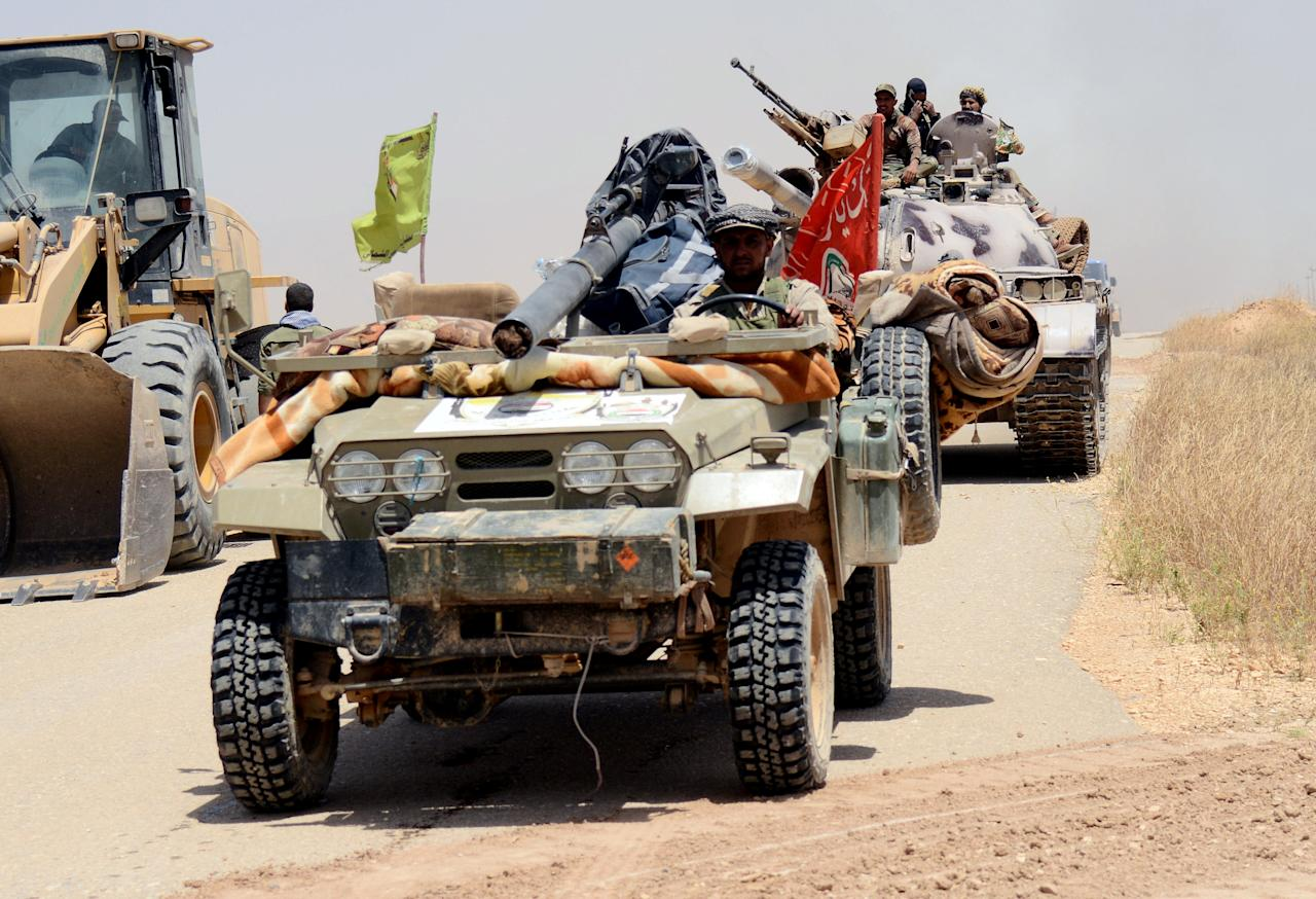 Popular Mobilization Forces (PMF) ride in military vehicles during a battle with Islamic State militants, at Um Jaris village on the Iraqi border with Syria, Iraq May 29, 2017.  REUTERS/Stringer EDITORIAL USE ONLY. NO RESALES. NO ARCHIVES