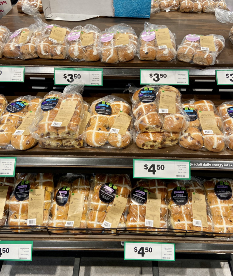 Photo shows hot cross buns on shelves in a Woolworths supermarket.