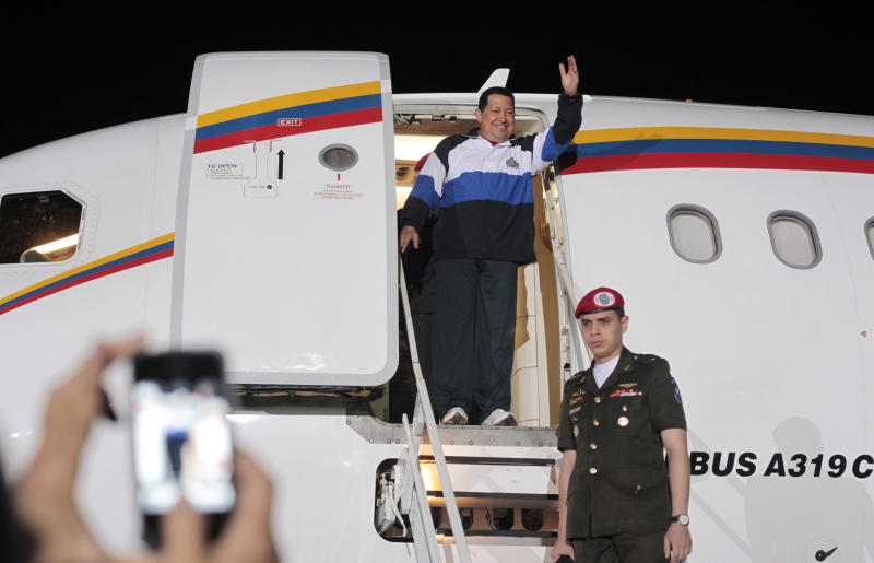 In this photo provided by Miraflores Presidential Press Office, Venezuela's President Hugo Chavez waves from his plane upon arrival to the airport in Barinas, Venezuela, Wednesday April 4, 2012. Chavez returned to Venezuela on Wednesday night after his latest round of radiation therapy treatment in Cuba. (AP Photo/Miraflores Presidential Office)