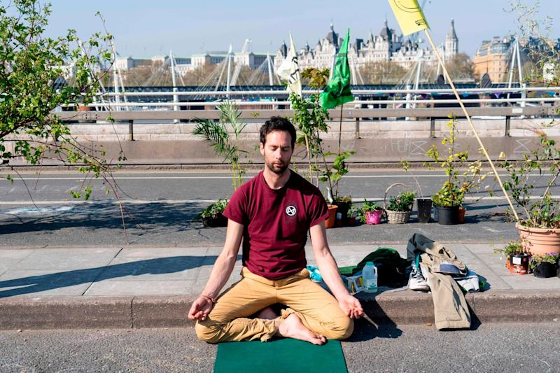 A climate change activist meditates as demonstrators continue to block Waterloo Bridge (AFP/Getty Images)