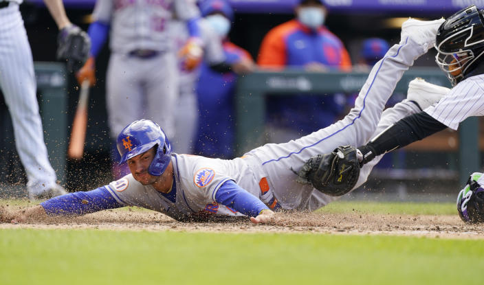 New York Mets pinch-runner Albert Almora Jr. scores on a pinch-hit double by Jonathan Villar as Colorado Rockies catcher Dom Nunez applies a late tag in the seventh inning of baseball game Saturday, April 17, 2021, in Denver. The Mets won 4-3 in the first game of a doubleheader. (AP Photo/David Zalubowski)