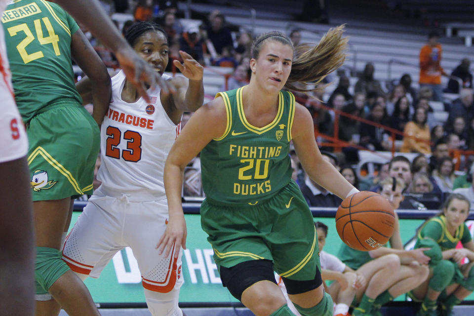 Oregon's Sabrina Ionescu, right, dribbles past Syracuse's Kiara Lewis, left, in the first quarter of an NCAA college basketball game in Syracuse, N.Y., Sunday, Nov. 24, 2019. (AP Photo/Nick Lisi)