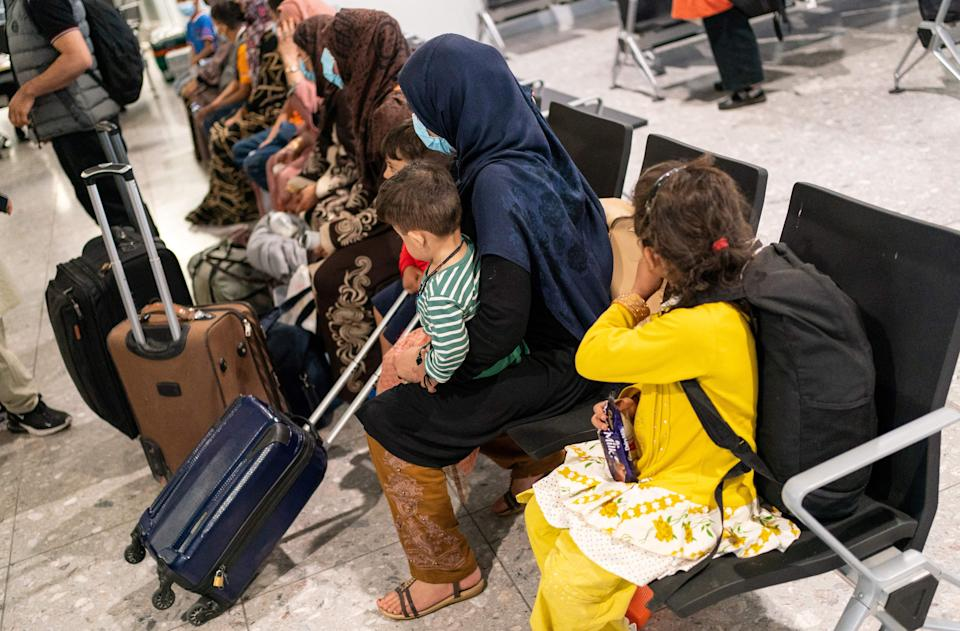 Afgan refugees wait to be processed after arriving on an evacuation flight from Afghanistan, at Heathrow Airport, London on August 26, 2021. - A terrorist threat against Kabul airport is