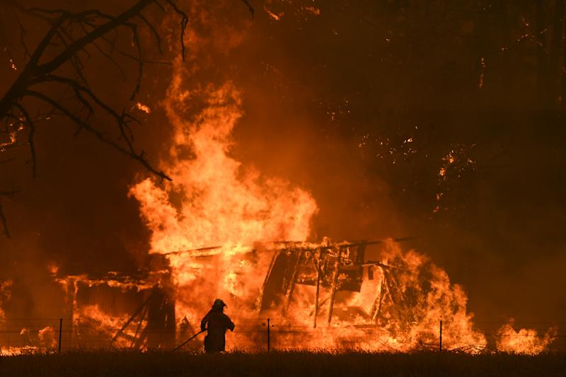 Firefighter battling the Gospers Mountain Fire as it impacted a structure at Bilpin last Saturday. Source: AAP