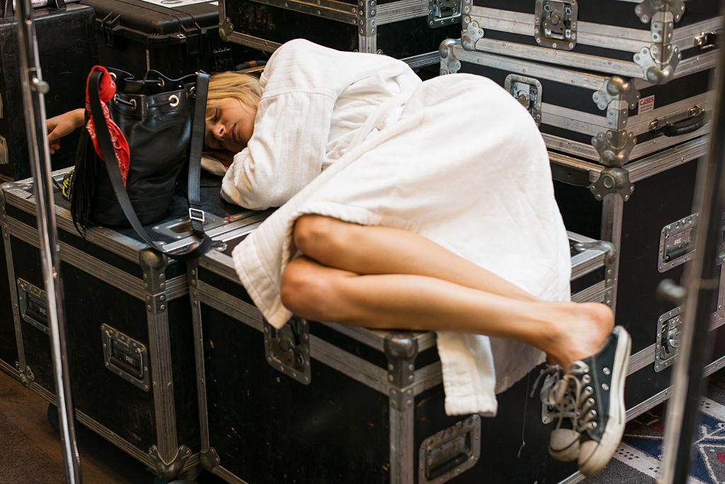<p>A model finds an awkward spot on top of lighting equipment for sleep before the Valentin Yudashkin show during Paris Fashion Week. (Photo: Getty Images) </p>