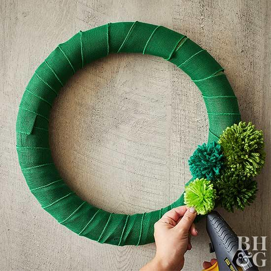 green wreath with yarn pompoms