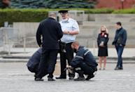 Investigators work in Red Square after an opposition activist reportedly simulated shooting himself in the head in a political protest, in Moscow