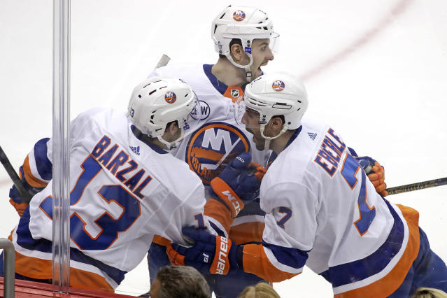 New York Islanders' Jordan Eberle (7) celebrates with Adam Pelech, center, and Mathew Barzal (13) after scoring against the Pittsburg Penguins during the first period in Game 4 of an NHL first-round hockey playoff series in Pittsburgh, Tuesday, April 16, 2019. (AP Photo/Gene J. Puskar)