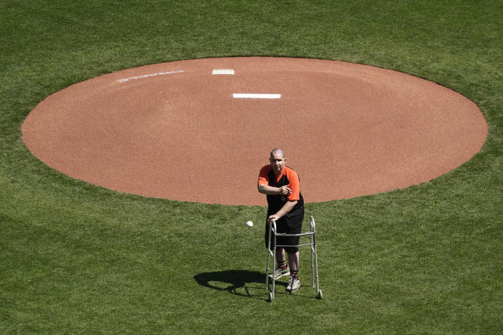 Bryan Stow throws out the ceremonial first pitch before an opening day baseball game between the San Francisco Giants and the Colorado Rockies, Friday, April 9, 2021, in San Francisco. Ten years ago Stow was attacked at Dodger Stadium. (AP Photo/Eric Risberg)