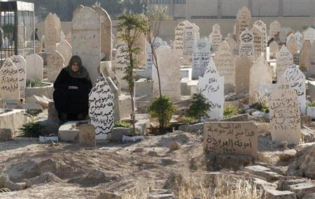 A woman prays near a grave as she visits a cemetery on the first day of Eid al-Adha in Raqqa