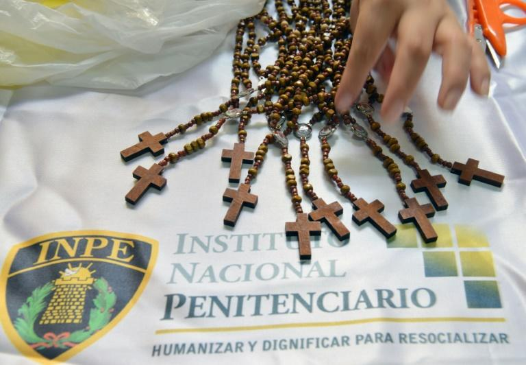 An inmate at the Virgen de Fatima Women's prison in Lima shows handmade wooden rosaries made by the prisoners. A total of 72 inmates in the prison have produced 33,000 rosaries to be sold at stores in Lima, to donate the proceedings to Pope Francis