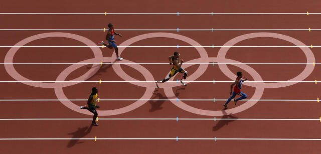 Oscar Pistorius (C) of South Africa runs with Luguelin Santos (R) of the Dominican Republic, Rusheen McDonald (L) of Jamaica and Maksim Dyldin of Russia during round 1 of the men's 400m heat 1 at the London 2012 Olympic Games at the Olympic Stadium August 4, 2012. Santos finished first with Pistorius coming second and Dyldin placing third. McDonald came in fourth. REUTERS/Pawel Kopczynski (BRITAIN - Tags: OLYMPICS SPORT ATHLETICS TPX IMAGES OF THE DAY) - RTR3632H