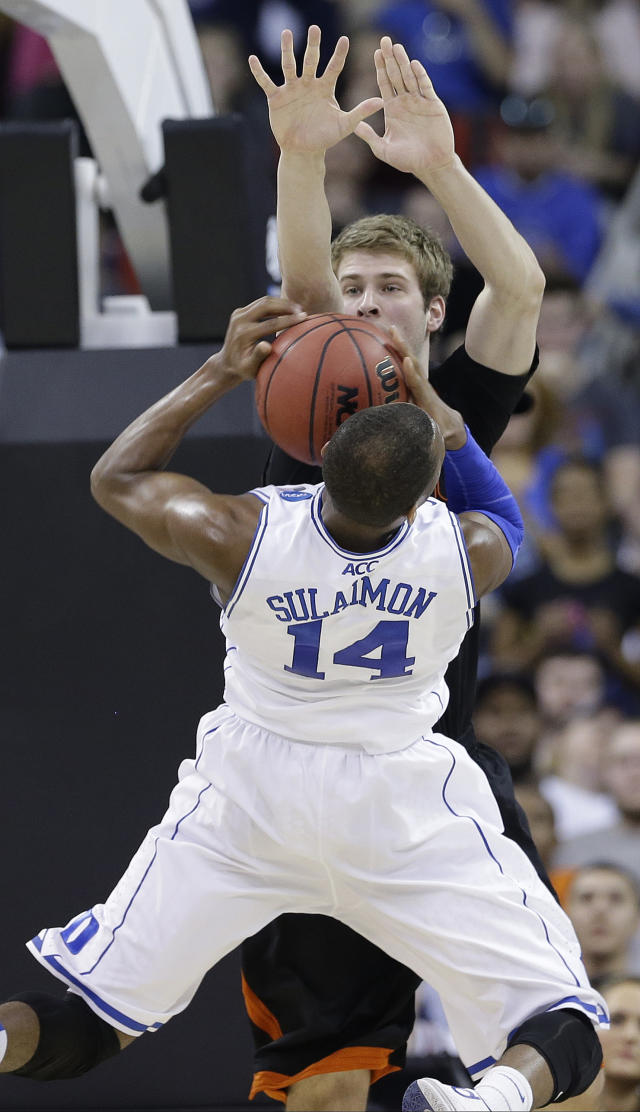 Duke guard Rasheed Sulaimon (14) tries to shoots against Mercer forward T.J. Hallice (14) during the second half of an NCAA college basketball second-round game, Friday, March 21, 2014, in Raleigh, N.C