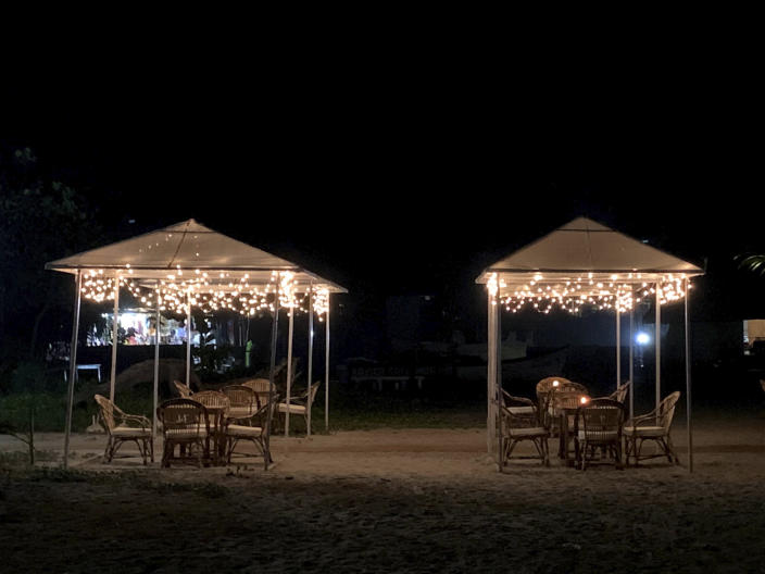 Empty shacks at the Morjim beach on the Arabian Sea coast at night in Goa, India, Dec.8, 2020. Along the popular beaches in North Goa from Candolim to Calangute to Morjim, many landmark coffee shops, tattoo parlors and shack bars with sunbeds have shut permanently. Nightlife in many popular party hubs has died. This holiday season in this Indian party hotspot, few visitors are enjoying its celebrated sunsets. The unspoken fear of the coronavirus is sapping Goa's vibrant beach shacks and noisy bars of their lifeblood. (AP Photo/Vineeta Deepak)