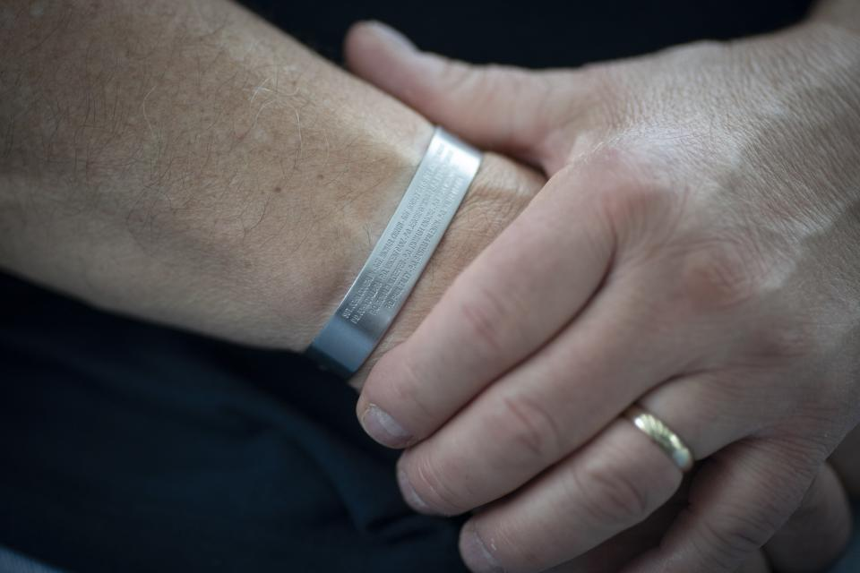 Retired NYPD Officer Mark DeMarco wears a wristband with the names of the 14 ESU members killed on Sept. 11, 2001, during an interview in his home in the Staten Island borough of New York on Tuesday, Aug. 3, 2021. He worries that the public memory of the attacks is fading, that the passage of time has created a false sense of security. (AP Photo/Wong Maye-E)