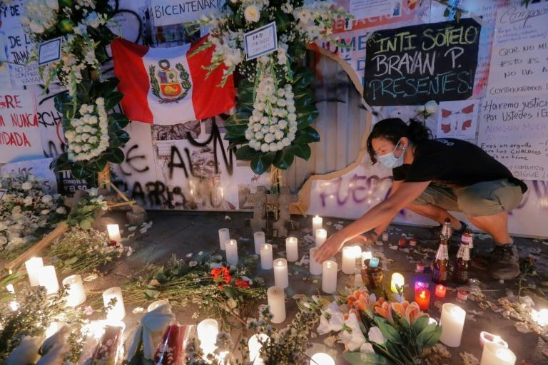 People light candles at a memorial for two people killed in street protests against interim president Manuel Marino, who resigned on Sunday