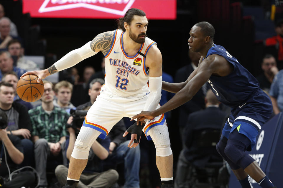 Oklahoma City Thunder's Steven Adams, left, of New Zealand keeps the ball at arms length form Minnesota Timberwolves' Gorgui Dieng, of Senegal, in the first half of an NBA basketball game Monday, Jan. 13, 2020, in Minneapolis. (AP Photo/Jim Mone)