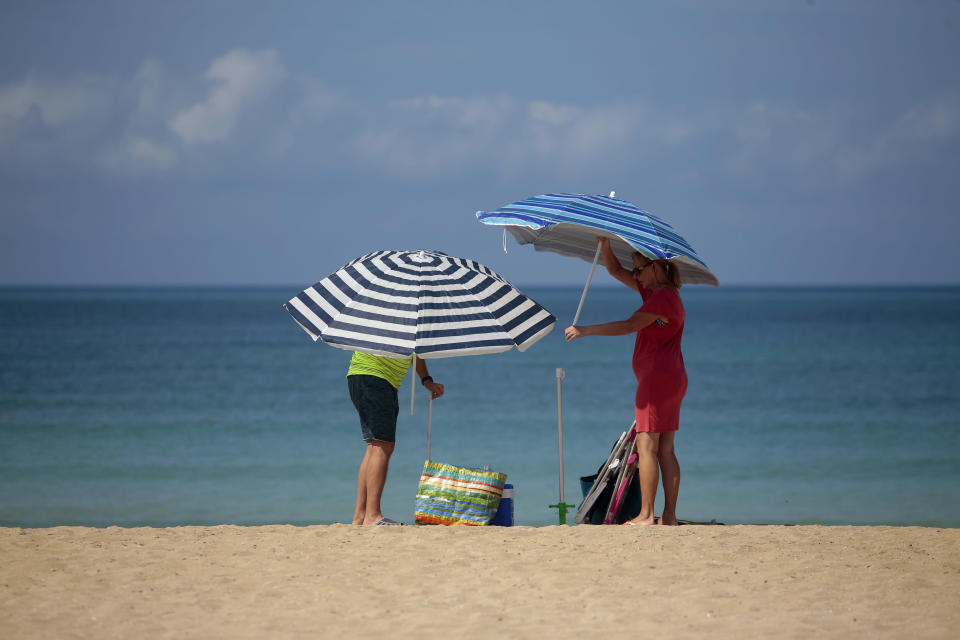 A couple adjust sunshades at the beach of Palma de Mallorca, Spain, Tuesday, June 16, 2020. Borders opened up across Europe on Monday after three months of coronavirus closures that began chaotically in March. But many restrictions persist, it's unclear how keen Europeans will be to travel this summer and the continent is still closed to Americans, Asians and other international tourists. (AP Photo/Joan Mateu)