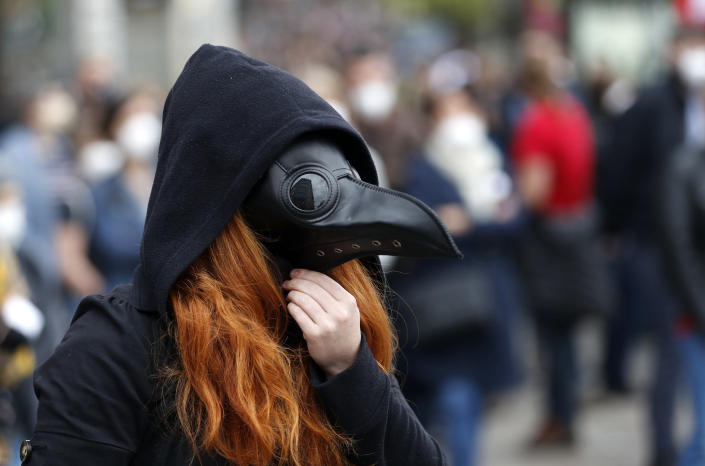 A woman adjusts her mask during a demonstration in Prague, Czech Republic, Thursday, April 29, 2021. Thousands of Czechs have rallied in the capital against President Milos Zeman, accusing him of treason for his pro-Russian stance over the alleged participance of Russian spies in a Czech huge ammunition explosion. (AP Photo/Petr David Josek)