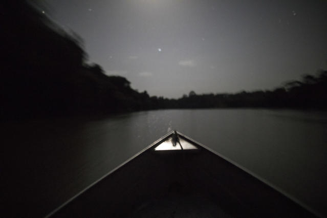In this Sept. 3, 2019 photo, moonlight illuminates the bow of a boat transporting indigenous leaders back to their villages after a gathering of Tembe tribes on the Alto Rio Guama Indigenous Reserve, in the Tekohaw village, in Para state, Brazil. Some had travelled long distances on dirt roads that cut through the lush jungle, or in boats along a muddy brown tributary of the Amazon River, all part of the Alto Rio Guama homeland that is officially protected but in practice under siege. (AP Photo/Rodrigo Abd)
