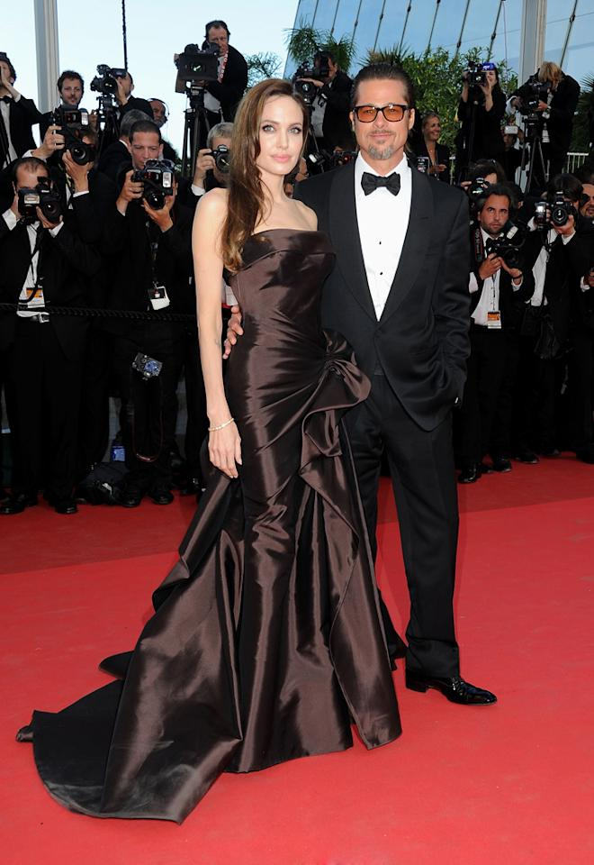 """What a difference a week -- and a continent -- can make. Just last Monday, Angelina and Brad turned the glam up to 10 at the Cannes Film Festival premiere of his movie, """"<a href=""""http://movies.yahoo.com/movie/1810022079/info"""">The Tree of Life</a>."""" Angelina was stunning in her Atelier Versace gown, and Brad showed that he can class it up when he wants to in his tux with bow tie. The only similarity between Brad's two looks is his salt-and-pepper goatee and Tom Ford sunglasses.   Click ahead to see the rest of the photos from this weekend's premiere of """"<a href=""""http://movies.yahoo.com/movie/1810090593/info"""">Kung Fu Panda 2</a>."""""""