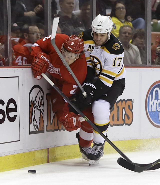 Boston Bruins left wing Milan Lucic (17) checks Detroit Red Wings defenseman Brendan Smith (2) during the first period of Game 3 of a first-round NHL hockey playoff series in Detroit, Tuesday, April 22, 2014. (AP Photo/Carlos Osorio)