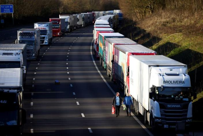 People walk by a line of parked lorries on the outskirts of Ashford