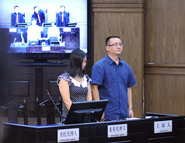 In this photo released by China's Xinhua news agency, Tang Hui, left, the mother of a young rape victim who sued a local authority for putting her into a labor camp, attends a court hearing in the Hunan Provincial People's High Court in Changsha, capital of central China's Hunan Province, Monday, July 15, 2013. The court Monday ruled in favor of Tang, a woman who last year was sentenced to 18 months in a labor camp for petitioning for harsher penalties for the men who raped and prostituted her 11-year-old daughter. The woman who became a symbol for the groundswell of opposition to China's labor camp system has won an appeal for compensation in a case that generated a huge public outcry. (AP Photo/Xinhua, Long Hongtao) NO SALES