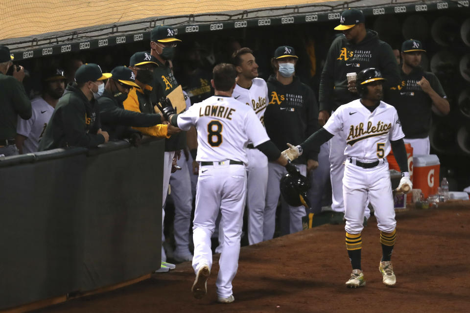 Oakland Athletics' Jed Lowrie is congratulated by teammates after scoring on a single by Seth Brown against the Tampa Bay Rays during the seventh inning of a baseball game in Oakland, Calif., Friday, May 7, 2021. (AP Photo/Jed Jacobsohn)