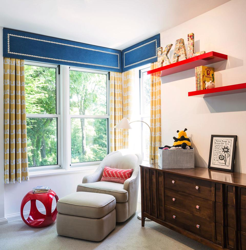 """<div class=""""caption""""> In another child's bedroom, McLeod was inspired by a comic book mural that runs along one of the walls. Even the vintage dresser has comic-themed drawer pulls that she sourced from <a href=""""https://www.etsy.com/"""" rel=""""nofollow noopener"""" target=""""_blank"""" data-ylk=""""slk:Etsy"""" class=""""link rapid-noclick-resp"""">Etsy</a>. """"It's little touches like that that I think really bring it to life,"""" she says. The valance is custom, with drapes from <a href=""""https://www.wayfair.com/"""" rel=""""nofollow noopener"""" target=""""_blank"""" data-ylk=""""slk:Wayfair"""" class=""""link rapid-noclick-resp"""">Wayfair</a>. The rocking chair is the client's own and the side table is also from Wayfair. </div>"""