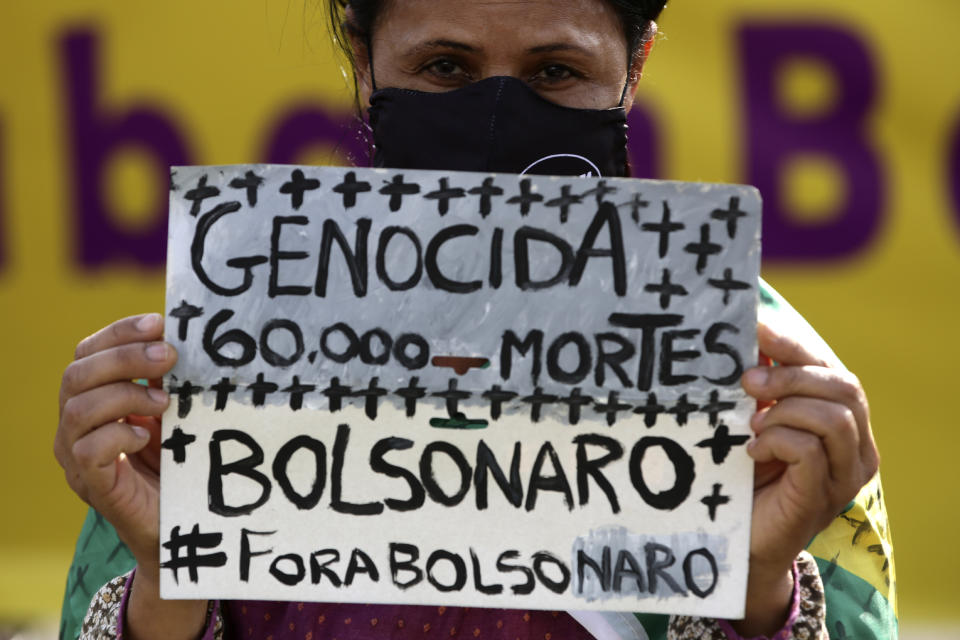 """A women's activist holds a sign that reads in Portuguese """"Genocide 60 thousand deaths, Bolsonaro out,"""" during a protest against the government's inefficiency in the face of the new coronavirus pandemic, in front of the National Congress, in Brasilia, Brazil, Thursday, July 2, 2020."""