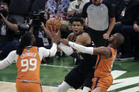 Milwaukee Bucks forward Giannis Antetokounmpo (34) is double teamed by Phoenix Suns forward Jae Crowder (99) and guard Chris Paul during the first half of Game 6 of basketball's NBA Finals Tuesday, July 20, 2021, in Milwaukee. (AP Photo/Aaron Gash)