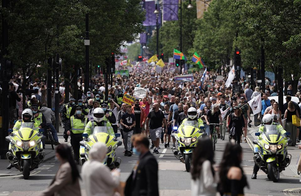 Protesters match down Oxford Street, flagged by police, during an anti-lockdown protest in London (PA)