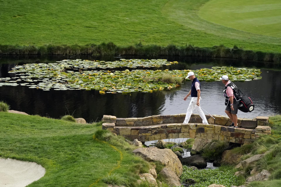Justin Thomas, left, walks with his caddie to the 18th green during the third round of the Zozo Championship golf tournament Saturday, Oct. 24, 2020, in Thousand Oaks, Calif. (AP Photo/Marcio Jose Sanchez)