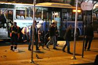 Investigators work near the wreckage of a bus at the scene of a suicide attack in Ankara on March 13, 2016
