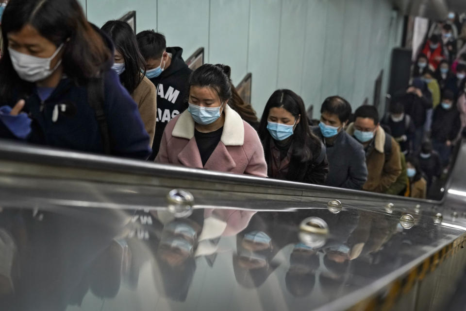 Commuters wearing face masks to help curb the spread of the coronavirus are reflected on a panels they ride an escalator at a subway station during the morning rush hour in Beijing, Tuesday, Nov. 17, 2020. (AP Photo/Andy Wong)