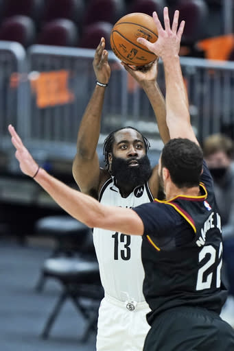 Brooklyn Nets' James Harden (13) shoots over Cleveland Cavaliers' Larry Nance Jr. (22) during the second half of an NBA basketball game, Wednesday, Jan. 20, 2021, in Cleveland. The Cavaliers won 147-135 in double-overtime. (AP Photo/Tony Dejak)