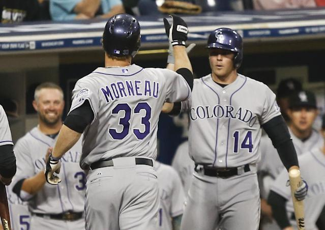 Colorado Rockies' Justin Morneau is greeted by Josh Rutledge, right, and Michael Cuddyer, left, after hitting a solo home run against the San Diego Padres in the second inning of a baseball game Wednesday, April 16, 2014, in San Diego. (AP Photo/Lenny Ignelzi)
