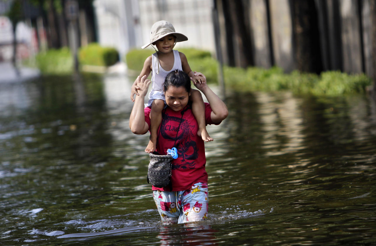 A Thai woman carries her daughter on her shoulders while wading through a flooded street in Bangkok, Thailand, Saturday, Nov. 5, 2011. Floodwaters lapped Bangkok's largest outdoor market Saturday as officials warned that there were no major barriers between the water and the heart of the Thai capital, less than 6 miles (10 kilometers) away. (AP Photo/Altaf Qadri)