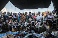 People fleeing violence in the Metekel zone gather outside a tent where clothes are being distributed at a camp in Chagni, Ethiopia
