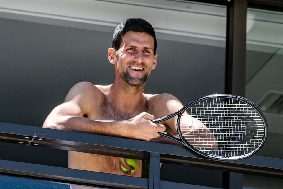 <p>Novak Djokovic smiles at fans from a hotel balcony in Adelaide</p> (Getty)