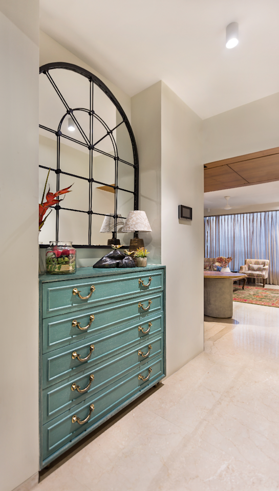 In the foyer, a niche presents an opportunity for neatly tucked away storage: a handmade, teak chest of drawers that's spruced up with an arched, metal-framed mirror and decor pieces.