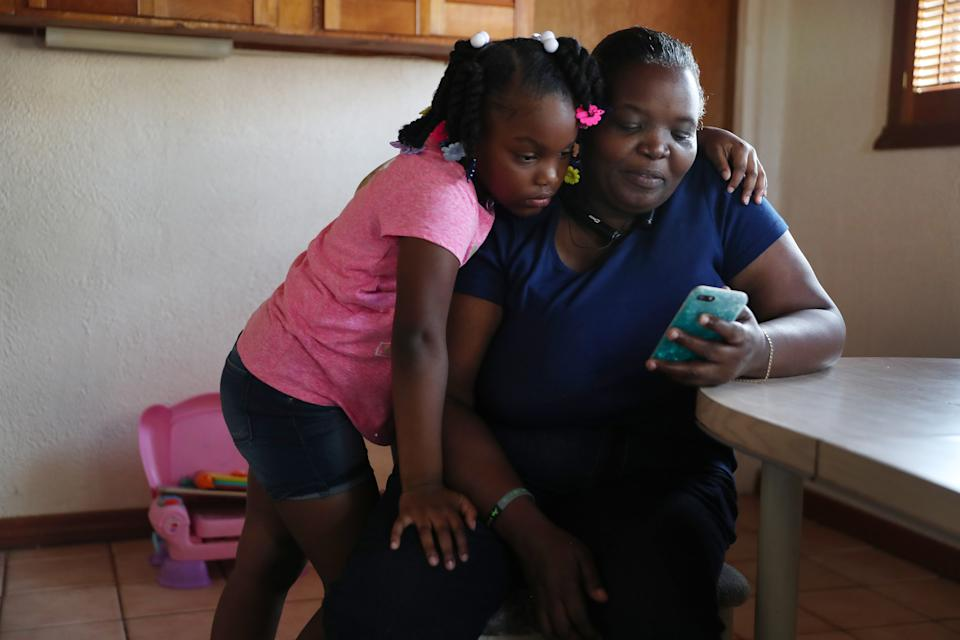 MIAMI, FLORIDA: Willie Mae Daniels spends time looking at videos with her granddaughter, Karyah Davis,6, after being laid off from her job as a food service cashier at the University of Miami. (Photo by Joe Raedle/Getty Images)