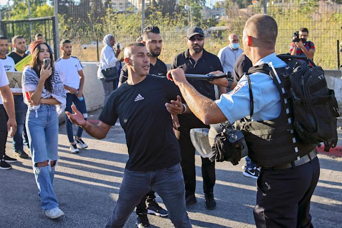 A Palestinian protester scuffles with a member of Israeli security forces near a roadblock at the entrance of the Sheikh Jarrah neighbourhood in east Jerusalem during a rally against the planned expulsion of Palestinians from houses there (AFP via Getty Images)