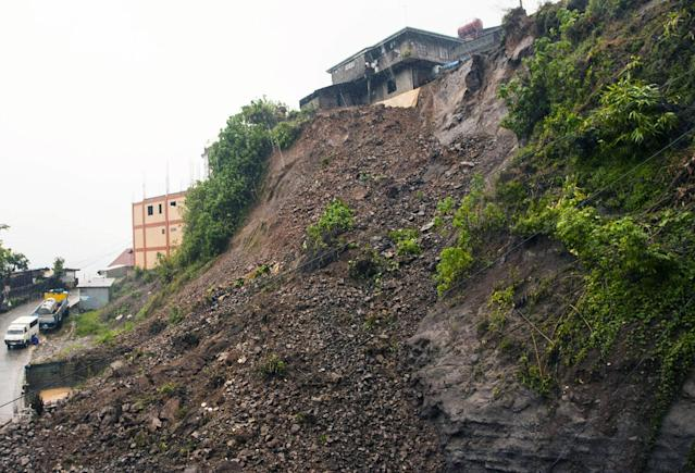 The soil is exposed at the site of a landslide in Baguio city as powerful typhoon Utor batters the northern Philippines Monday, Aug. 12, 2013, toppling power lines and dumping heavy rain across mountains, cities and food-growing plains. The storm killed at least one man in a landslide and left 45 fishermen missing. Typhoon Utor, described as the strongest globally so far this year, slammed ashore in mountainous eastern Aurora province with sustained winds of 175 kilometers (109 miles) per hour and gusts of up to 210 kph (130 mph). (AP Photo)