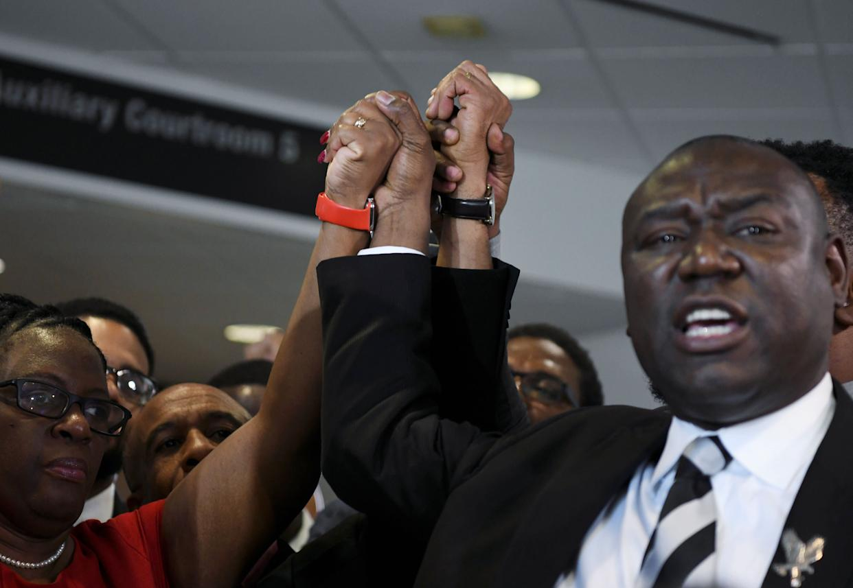 Botham Jean's mother, Allison Jean, and his father, Bertram Jean, raise their hands with their family attorneys Daryl Washington, Benjamin Crump and Lee Merritt after Guyger's murder conviction was delivered on Oct. 1, 2019. (Photo: Jeremy Lock / Reuters)