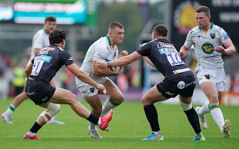 Northampton's Ollie Sleightholme (centre) is tackled by Exeter Chiefs Joe Simmonds (centre right) and Sam Hidalgo-Clyne (left) during the Gallagher Premiership match at Sandy Park, Exeter. - PA